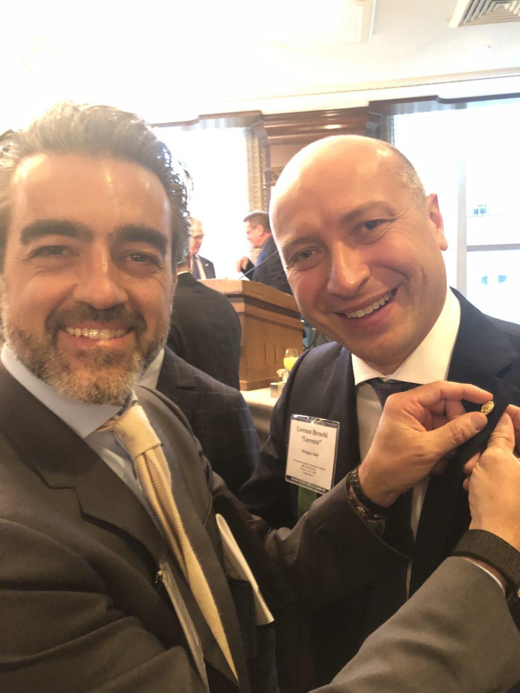 Andrea attacca la spilla di Associate Member al Prof. Lorenzo Breschi